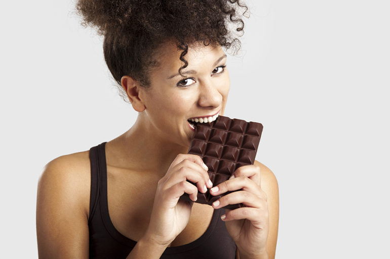 Beautiful african woman holding and eating a huge dark chocolate bar
